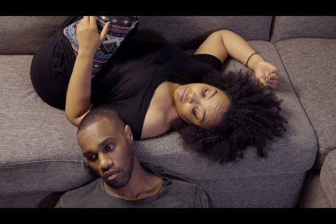 Black man in grey shirt next to Black woman upside down in black shirt on grey sofa