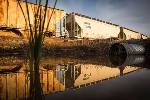 Train cars sit next to miles of unused pipe (unseen), prepared for the proposed Keystone XL pipeline, on October 14, 2014, outside Gascoyne, North Dakota.