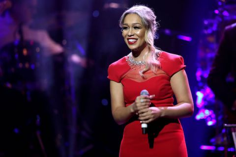 Black woman with blonde hair smiles in red dress against blurry blue-purple-lit background