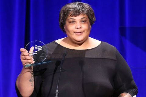 Black woman in black dress holding clear award statue behind brown podium with purple sign against blue curtain background