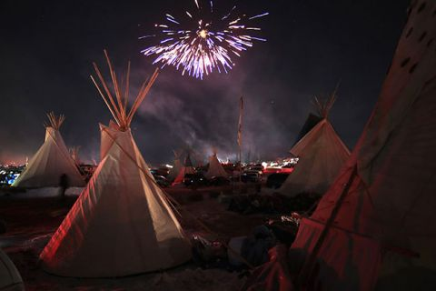 Fireworks fill the night sky above Oceti Sakowin Camp as activists celebrate after learning an easement had been denied for the Dakota Access Pipeline near the edge of the Standing Rock Sioux Reservation on December 4, 2016, outside Cannon Ball, N.D.