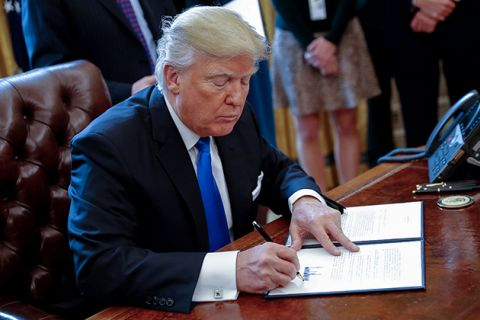 President Donald Trump signs one of five executive orders related to the oil pipeline industry in the Oval Office of the White House January 24, 2017, in Washington, D.C.