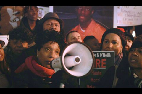 Black woman in black jacket and red scarf holding white megaphone in front of supporters holding black and white signs with multi-colored text and an enlarged photograph of a Black man in an orange shirt