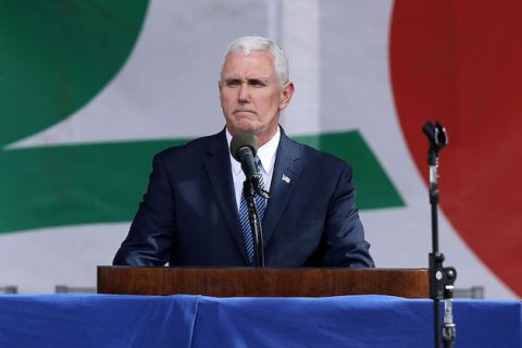 White man with white hair at a podium