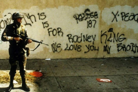 Man in green camouflage uniform and helmet holding black assault rifle in front of brown wall with black graffiti
