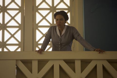 Black woman in grey and white dress stands behind white balcony and in front of white wall with yellow sunlight streaming through window