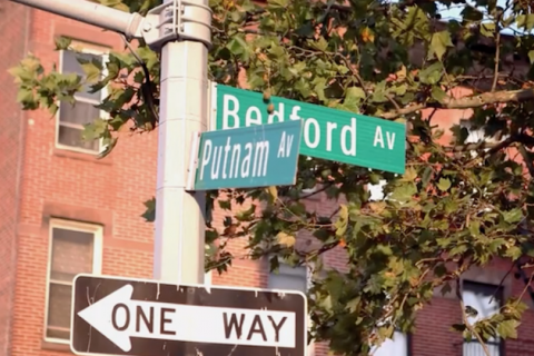 Green street signs with grey text on grey pole with black-and-white street sign in front of red brick building
