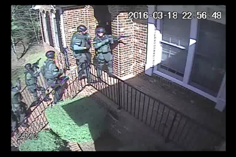 White men in green tactical gear line up outside red brick house on green lawn