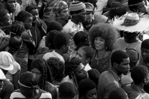 Angela Davis (center, with Afro and black-striped shirt) at a 1982 carnival in Grenada,