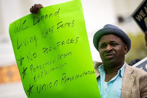 "Black man holds sign that reads: ""We demand living wage fares, no pool fare, protection from exploitation, union representation."""