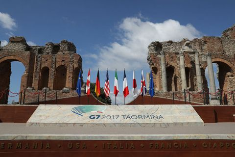 Flags of the G7 group of nations, as well as the flag of the European Union, stand on a stage in the ancient amphitheater prior to the beginning of the G7 Taormina summit on the island of Sicily on May 26, 2017, in Taormina, Italy.
