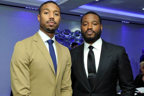 Black man in khaki suit and blue tie next to Black man in black suit and tie in front of blue-lit white wall and ceiling