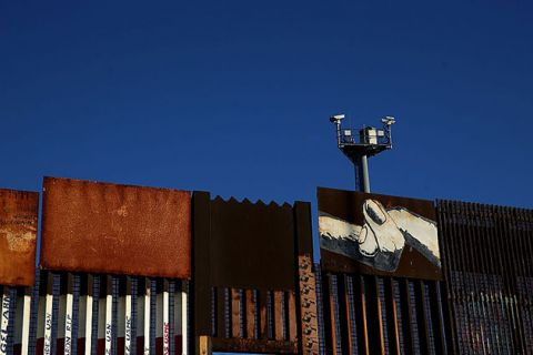 Surveillance cameras stand above the US-Mexican border fence at on January 27, 2017, in Tijuana, Mexico.