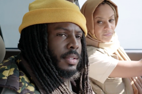 Black man in yellow beanie and green camouflage jacket sits next to Black woman in pink headscarf and