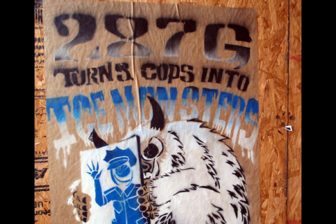 "Spray painted sign reads: ""287g turns cops into ICE monsters."""