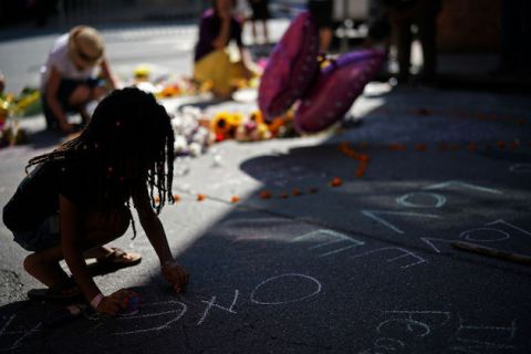 Black girl writes on ground using chalk