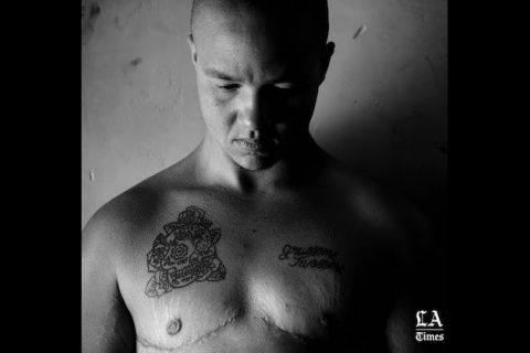 Black-and-white image of Black and Brown boer without shirt and grey tattoos in front of grey wall fading into black