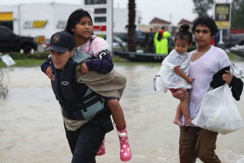 Evacuees are helped to dry land after their homes were inundated with Hurricane Harvey on August 28, 2017 in Houston, Texas.