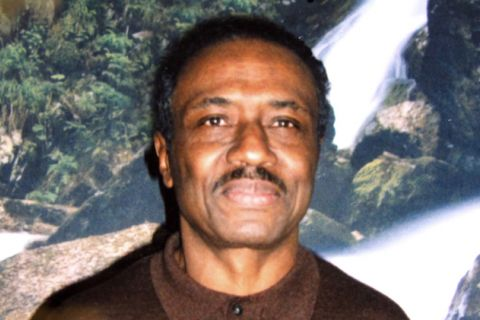 A Black man with a mustache wearing a brown shirt in front of a photo backdrop with trees and a waterfall
