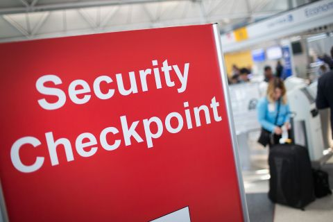 "In an airport, a red sign with white writing that says ""Security Checkpoint"""