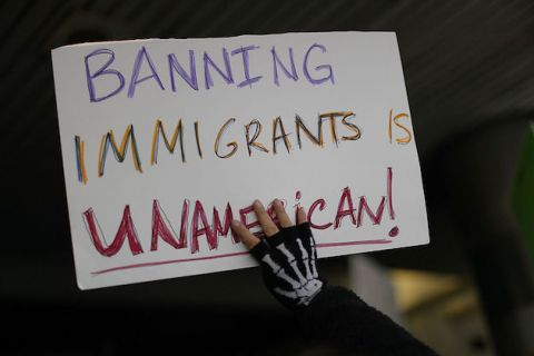 "A protester holds up a sign that reads, ""Banning Immigrants is UnAmerican!"""