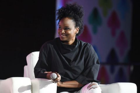 Black woman in black sweater and white jeans sits on white chair in front of blurry black and purple screen with multicolored insignia