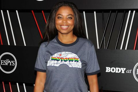 Black woman in light blue shirt with multicolored rainbow text and white insignia stands in front of black wall with white and red lines and white insignia