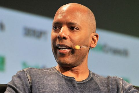 Black man in grey sweater with brown headset microphone in front of grey and white screen