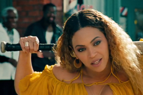 Beyoncé in yellow, holding a bat