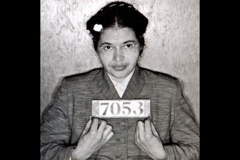 Black-and-white image of Black woman in grey coat holding black sign with white numbers in front of grey wall