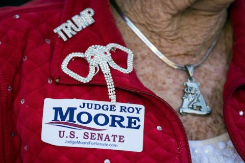 "Woman wears ""Trump"" pin and ""Judge Roy Moore U.S. Senate"" sticker"