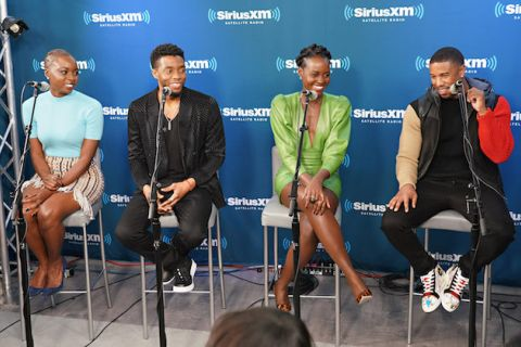 Black woman in light blue shirt and brown and orange plaid skirt sits next to Black man in black suit next to Black woman in green dress next to Black man in black and red and brown jacket and black pants in front of blue screen with white text