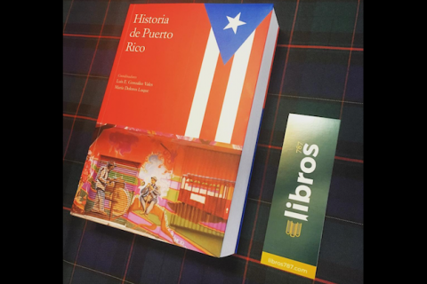 Book with red cover and red and white and blue Puerto Rico flag and white text next to dark green sticker with white and yellow text on top of navy and black and green plaid cloth with red and yellow lines
