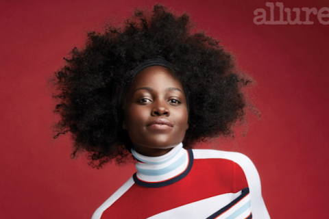 Black woman with black afro in red and white and navy dress in front of red background