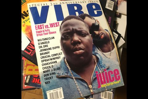 Magazine cover with two Black men in blue denim on white background with blue and pink and black text on top of multicolored magazines on brown table