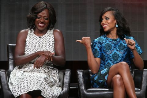 Black woman in white dress with black pattern laughs while sitting in black chair next to Black woman in blue and black dress who smiles while sitting in black chair in front of black screen