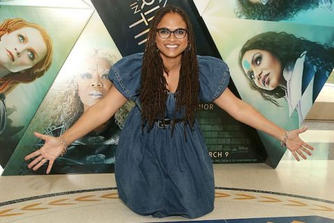 Black woman in black glasses and blue denim dress kneels in front of movie poster with Black and Brown and White women and gold text on black background on brown floor
