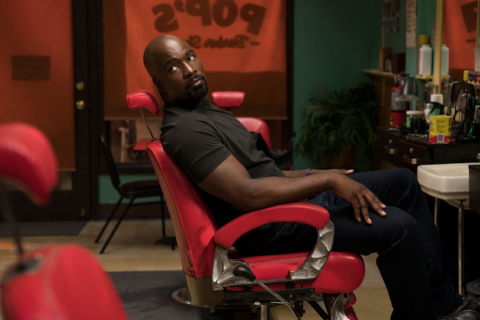 Black man in grey shirt and black jeans sits in red chair in front of teal and brown wall and doorframe