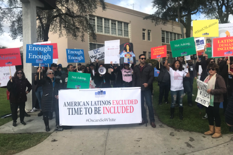 Brown women and men hold multicolored signs near white banner with blue and black and red text on grey stone pavement and green grass in front of brown building