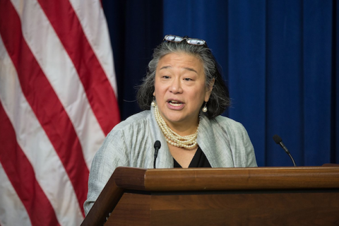 Asian woman with black hair in black glasses and grey sweater and black undershirt speaks behind brown podium with black microphones and in front of blue curtain and red and white and blue U.S. flag