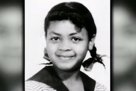 Black and white photo of smiling little Black girl with pigtails