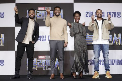 Black in black suit and white shirt stands next to Black man in beige sweater and blue jeans next to Black woman in grey dress next to Black man in beige jacket and blue jeans in front of black and white wall with blue text