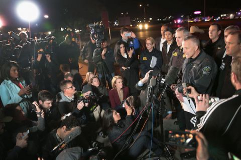 Man in police uniform addresses large crowd of press outside in the dark
