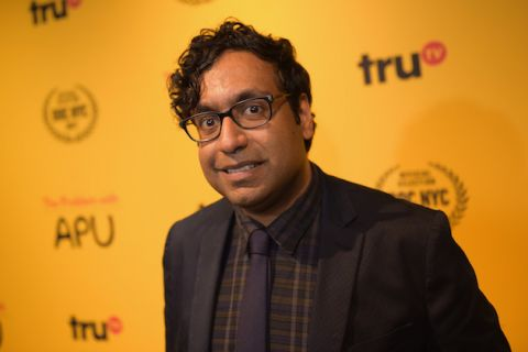 Brown man with black hair in black glasses and navy suit with brown and green shirt smiles in front of yellow wall with black and red text and logos