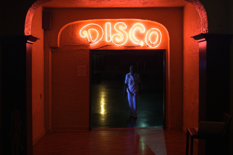 Black woman in blue light near yellow light inside dark doorway with red neon sign