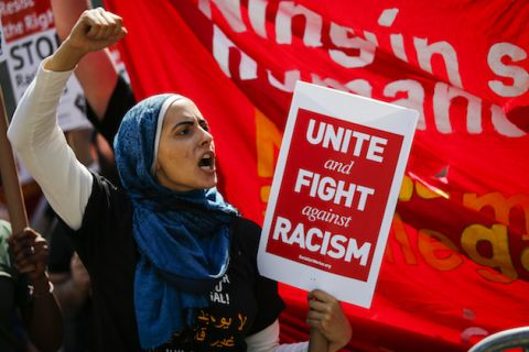 Brown woman in black t-shirt and blue hijab holds red sign with white text in front of red flag with white text