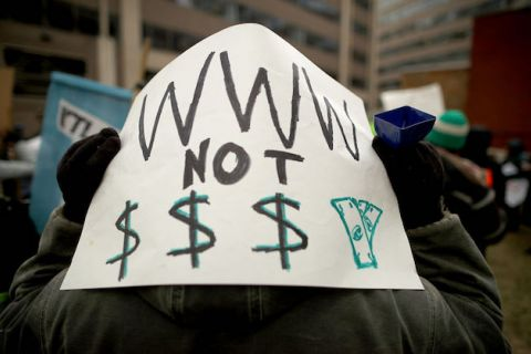 "Someone holds sign on back of their head that reads, ""WWW not $$$"""