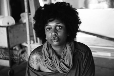 Black-and-white image of Black woman with black afro and septum and lip piercings in scarf and shirt with tattoos on right shoulder in front of grey wall and boxes
