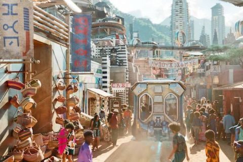 Open marketplace with brown dirt pathway and Black women and men in multicolored clothing in front of grey buildings and green mountains