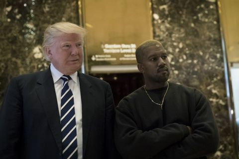 Donald Trump and Kanye West. White man with blonde hair in black and white suit and tie stands next to Black man with blonde hair in black shirt and gold necklace in front of gold and grey stone elevator and lobby walls